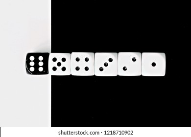 Game cubes are next to each other. Five white dice range from one to five in a row on a black background, the sixth dice is black on a white background - concept with contrast and dice
