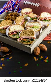 Game day football party table with  sub sandwich and snacks.