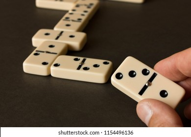 A game of dominoes on a dark table . The concept of the game of dominoes. Man's hand with a Domino. Close up.