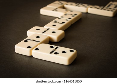 A game of dominoes on a dark table . The concept of the game of dominoes. Close up.