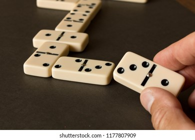 A game of dominoes on a dark table . The concept of the game of dominoes. Man's hand with a Domino. Close up