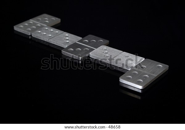 A game of dominoes in progress. Dominoes are metal and on a reflective black background.
