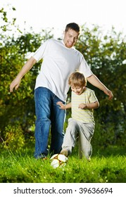 Game in football of father and son on a summer lawn