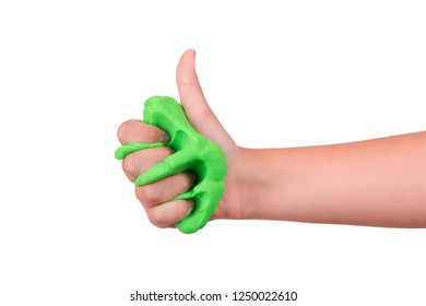 The game is green slime. The child crushes the slime in his hand. Slime sandwiched in hand.
