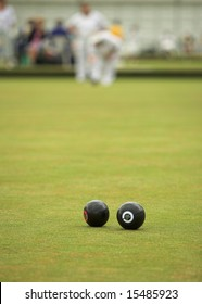 A game of lawn bowls. Focus on the woods.