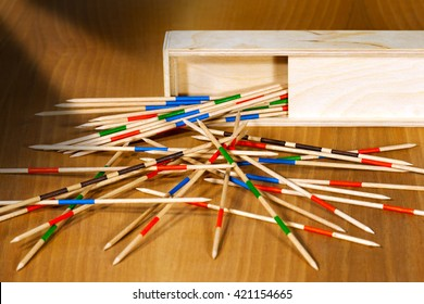 Game of mikado or shanghai with wooden sticks and box, on a brown table