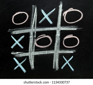 The game of naughts and crosses being played on a black board.