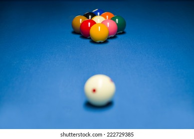 Game of nine ball in distance, on blue table cloth for a tournament in europe