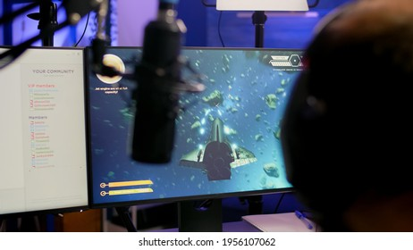 Game over for pro streamer playing online vide game space shooter in streaming room using modern headseat. Cyber performing on powerful pc talking with players on chat open during professional