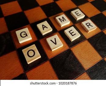 Game over. Wooden letter tiles on wooden chessboard