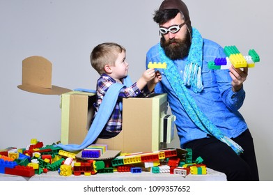 A game of pilots. Father and son are at home. Avicacy concept. Airplane and pilot. Happy child plays with father. Game and entertainment. Dream of the future. Child development. A toy plane