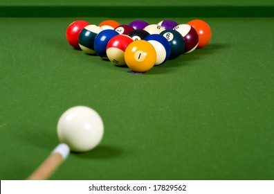 A game of pool with the balls lined up in an 8-ball formation on a green felt pool table