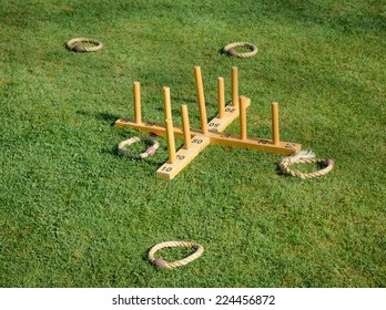 """A game of quoits or hoopla in the summer sun on a  lawn. """"Missing the target"""""""