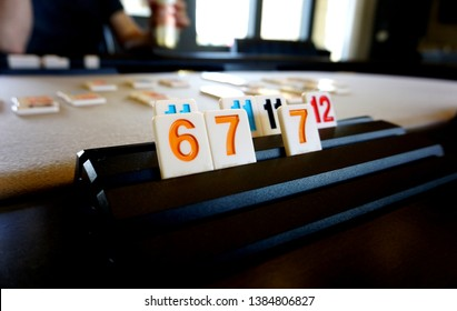 Game of rummy in progress showing board game large blocks with numbers 6, 7, 11 and 12 on the player's game tray with other pieces on the table and an glimpse of an opponent in the background.