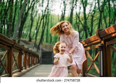 Spiel des Tags. Frohe junge Mutter, die nach ihrer Tochter im Park im Park herrengt