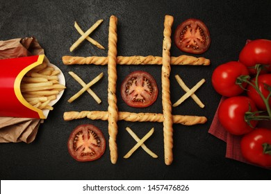 Game of tic tac toe of french fries and tomatoes. Choosing healthy vs unhealthy foods. Fit or fat concept.