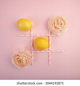 A game of tic tac toe with lemons and peony soft pink flowers on pastel pink background, creative art - Shutterstock ID 2044192871