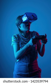 The game vr. The girl in the helmet and the controller plays a game with creative light. concept of cyber sports. games. viral reality