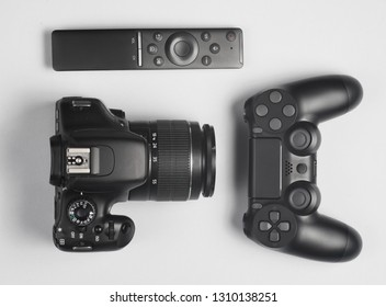 Gamepad, Dslr camera, tv remote. Modern gadgets and devices on gray background.  Top view.