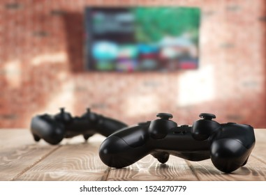 Gamepads on the table and TV on the background