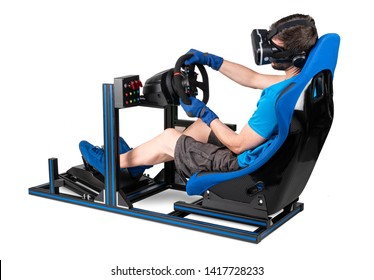 gamer in blue tshirt with VR virtual reality glasses training on simracing aluminum simulator rig for video game racing. Motorsport car bucket seat steering wheel pedals isolated on white background