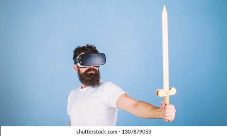 Gamer concept. Guy with head mounted display holds sword, play fighting game in VR. Hipster on serious face enjoy play game in virtual reality. Man with beard in VR glasses, light blue background.