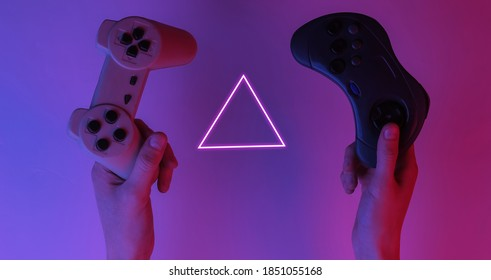 Gamer concept. Hands holding gamepads. Creative pop art pink blue neon color. Trendy gradient illumination. Night light