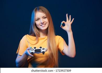 Gamer girl. Happy girl holding video game joystick showing OK sign, on blue background