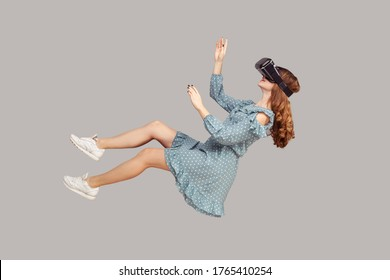 Gamer girl in ruffle dress hovering in air, levitating with virtual reality glasses on head, playing game through vr headset, floating in cyberspace. indoor studio shot isolated on gray background