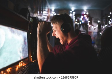 Gamer in his headphones emotionally rejoices in victory,looks at the computer screen. Portrait of an emotional young man playing video games at night on a computer in a cozy room at home and rejoicing