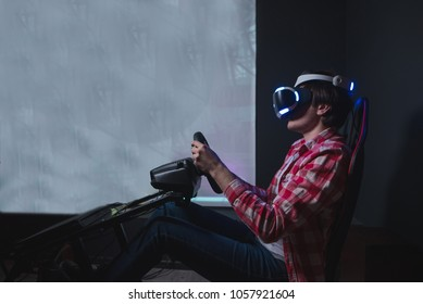 Gamer plays VR race on a black background. Virtual reality on car simulator. A man is sitting behind a car simulator and plays games in VR glasses.