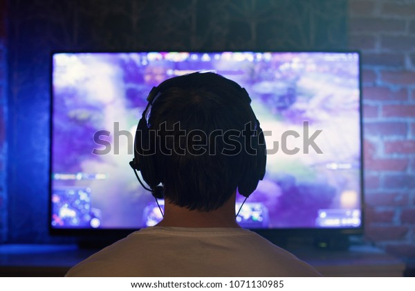 Gamer or streamer in earphones with microphone sits at home in dark room and plays with friends on networks in video games. A young man sits in front of a monitor or TV.