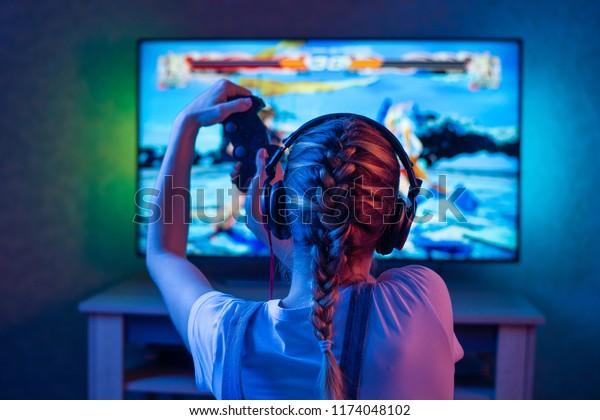 Une joueuse ou une fillette de musique à la maison dans une pièce sombre avec une gamepad jouant avec des amis sur les réseaux en jeux vidéo. Un jeune homme est assis devant un écran ou une télé.