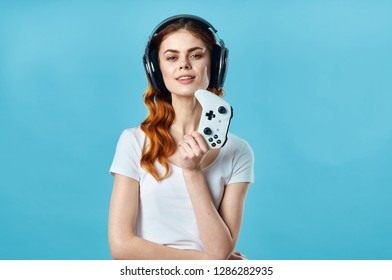 Gamer woman in headphones and with a joystick in his hand