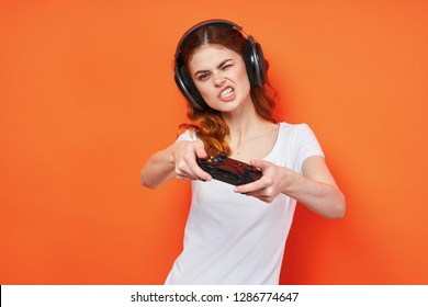 A gamer woman with a joystick and headphones bared teeth against an orange background