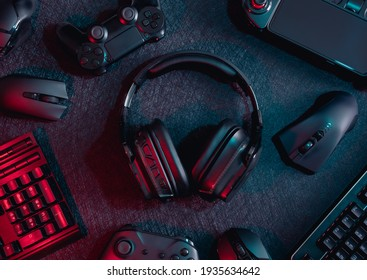 gamer work space concept, top view a gaming gear, mouse, keyboard, joystick, headset with rgb color on black table background.