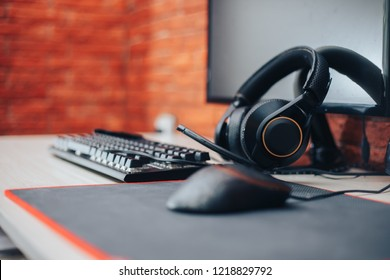 gamer workspace concept, gaming gear, mouse, keyboard in ear headphone and mouse pad on table background. focuse on headphones selected focuse