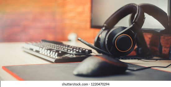 gamer workspace concept, gaming gear, mouse, keyboard in ear headphone and mouse pad on table background. focuse on headphones selected focuse long banner