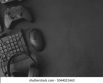 gamer workspace concept, top view a gaming gear, mouse, keyboard, joystick, headset on black table background with copy space.