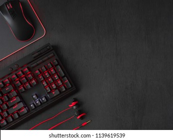 gamer workspace concept, top view a gaming gear, mouse, keyboard, joystick and mouse pad on black table background with copy space.