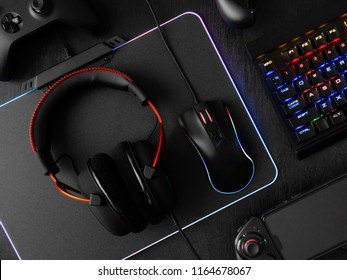 gamer workspace concept, top view a gaming gear, mouse, keyboard, joystick, headset, mobile joystick and mouse pad on black table background with RGB color.