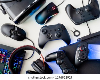 gamer workspace concept, top view a gaming gear, mouse, keyboard, joystick, headset and mouse pad on white table background.