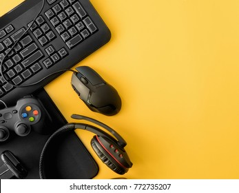 gamer workspace concept, top view a gaming gear, mouse, keyboard, joystick, headset, on yellow table background with copy space