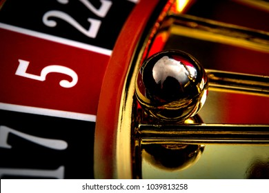 Games of chance, nightlife and casino gambling concept with a macro close up on the roulette ball in the wheel that indicates five red as the winning number