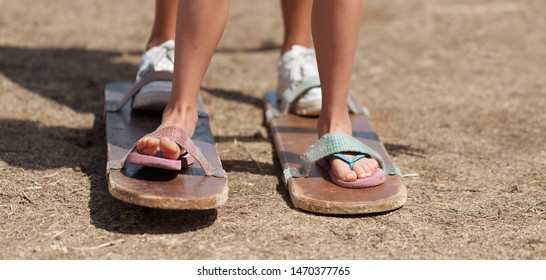 Games clogs race, two team members stand on two wooden planks with their feet tied to the plank