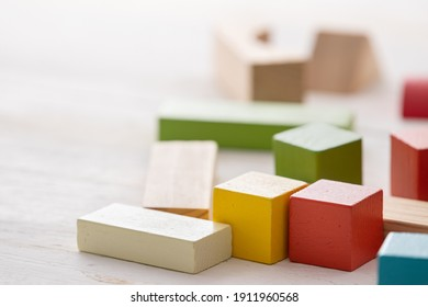 Games with colorful wooden bricks on a white wooden table. The child plays with geometric shapes made of natural wood. Learning and education concept.