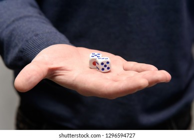 Games dice in hand. Man offers to play board games