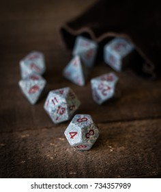 Gaming dice on a wooden table top being rolled out of a bag shot in natural light with subdued wood grain colors as background.
