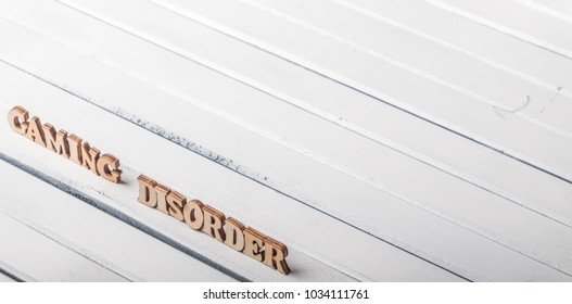 'Gaming Disorder' text on white wooden table top.