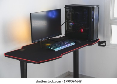 Gaming PC in a gaming desk. The pictures shows a complete computer for a gamer, with a fast response monitor, RGB lights, keyboard, mouse and a case.